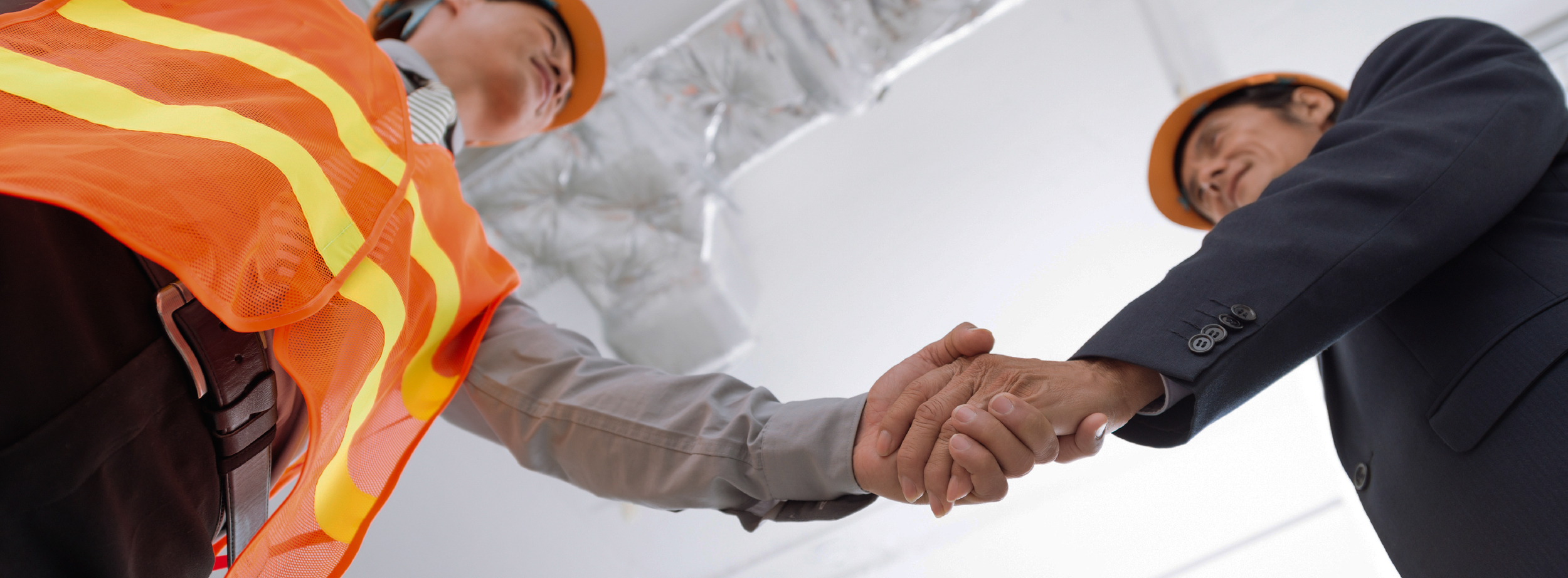 Construction man and businessman shaking hands